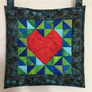 A quilt hanging on a wall with a red heart in the middle